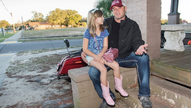 Kailee Fullen, 7, listens as her father John Fullen discusses his views about potential use of the former site of the W.A. Blount Junior High School that is across the street from their home on West Gregory Street in Pensacola.