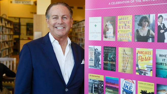 ancho Mirage Writers Festival Chairman Jamie Kabler poses beside a promotion for the Rancho Mirage Writers Festival in 2017.