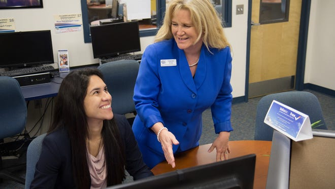 Indian River State College professor Arlene Green (right) discusses the effective use of social media with recent graduate Yamilet Cendejas.