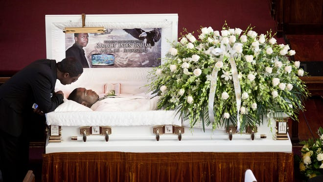 In this Feb. 18, 2012, file photo, Franclot Graham leans over his son, Ramarley Graham, in his casket before funeral services in the Bronx borough of New York.