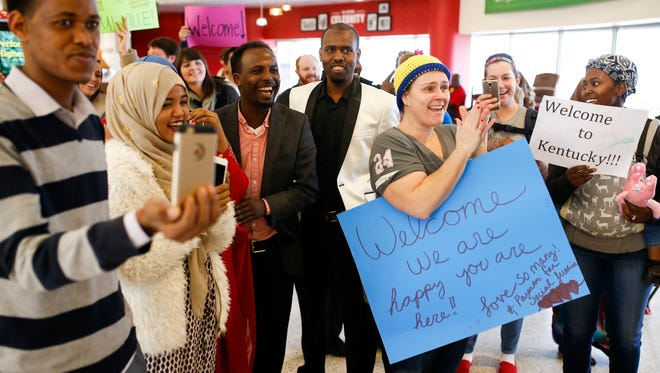 Barkat Mohamed, center left, laughs and cheers with friends and family as his wife, Zemzem Abib, and his daughter, Khadra Muse, to arrive from Ethiopia at the Louisville airport Friday. Feb. 3, 2017