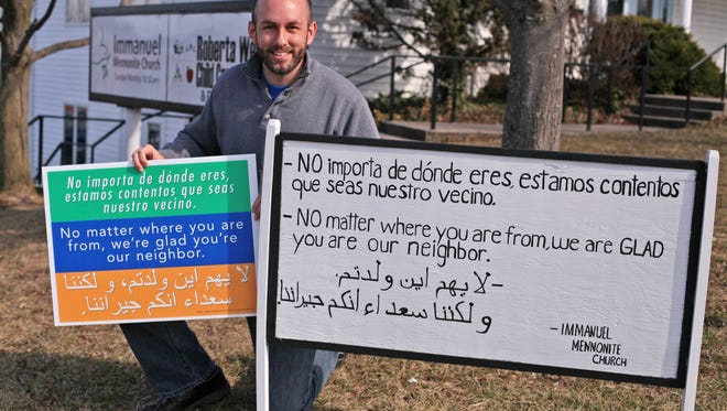 Matthew Bucher, pastor at Immanuel Mennonite Church in Harrisonburg, kneels by the original hand-painted sign in front of the church on Feb. 2, 2017 that was the inspiration for the green, blue and orange welcome signs that now are in yards across the country.