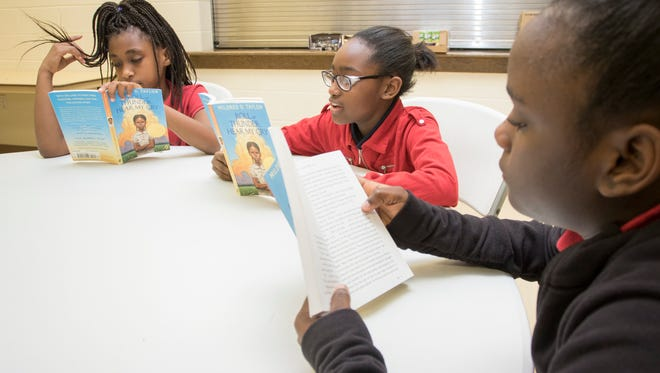 Kalisha Ross, 10, left to right, Dymijah Johnson, 11, and Eymijah Johnson, 11, participate in a literature circle during the Play, Learn, Grow after school program at the Wedgewood Community Center in Pensacola. The after-school program will present a special spring break program March 20-24.