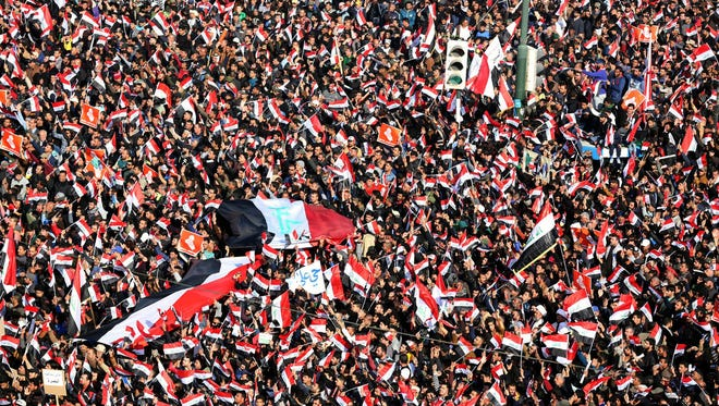 Supporters of Iraqi Shiite cleric Muqtada al-Sadr wave national flags and chant slogans during a demonstration at al-Tahrer square, central Baghdad, Iraq, on Feb. 11, 2017. 1