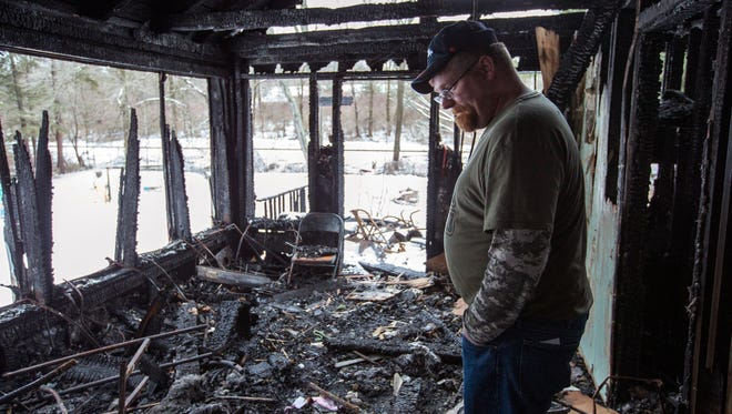 Mike Chandler walks through the ashes of his Whitney Point home on Jan. 24, 2017. Mike, his wife Nicole, their six young children, and Nicole's father managed to escape the fire that destroyed their house and all of their possessions.