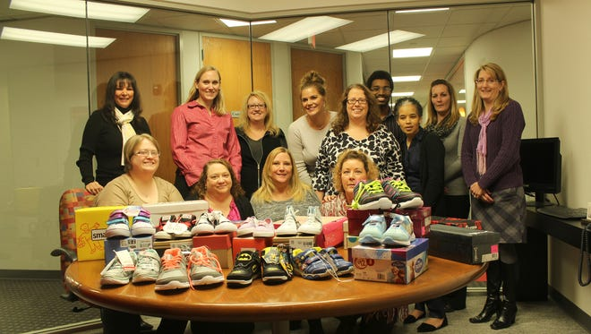 Sibcy Cline Mortgage Services pooled their money to purchase over 50 pairs of shoes for the 'Sweet Soles For Love' campaign. With the shoes are: from left (front row) Ryshel Bowling (Williamsburg), Lisa Hodson (Mason), Rita Smith (Deer Park), and Dorothea Burke (Mason); (second row) Beth Price (Anderson Township) and Mary Hill (Colerain Township); (back row) Pat Kuether (Ft. Wright), Julie Menning (Sharonville), Juanita Lovins-Hottle (Deer Park), Leigh Southard (Norwood), Mark McDaniel (Deer Park), Rikki Earls (Milford) and Diane Britt (Mason).