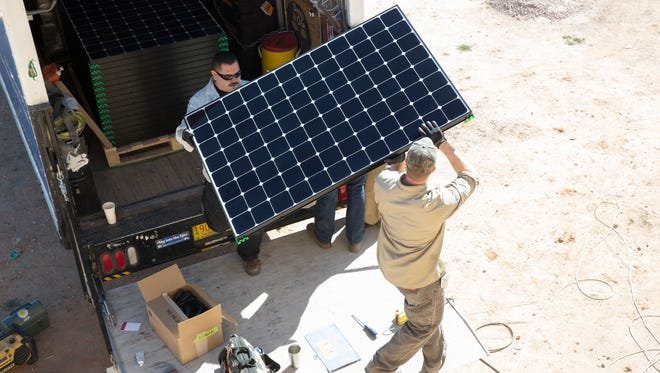 Ben Duerksen, right, and Romero Hernandez with Positive Energy Solar, pull solar panels from a truck as they prepare to install them on a customers home. Wednesday, February 22, 2017.
