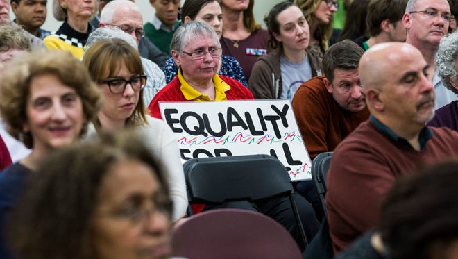 Alice Baker holds a sign during a town hall meeting with congresswoman Brenda Lawrence at the Samaritan Center in Detroit on February 23, 2017.
