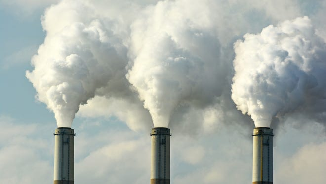 Multiple coal fossil fuel power plant smokestacks emit air pollution.