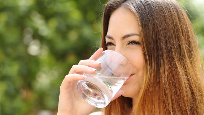 Healthy woman drinking fresh water from a glass outdoors.