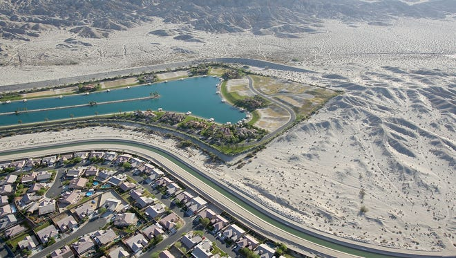 The Coachella branch of the All-American Canal snakes between a housing development and a man-made water-ski lake next to the open desert in north Indio.