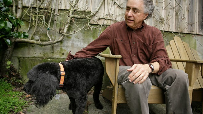 In this photo taken Wednesday, Feb. 15, 2017, Michael Fasman sits with his dog Hudson outside his home in San Francisco. As more states legalize marijuana for humans, more pet owners are giving their furry companions cannabis-based extracts, ointments and edibles marketed to treat everything from arthritis and anxiety to seizures and cancer.