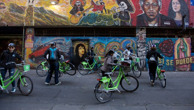 Members of the Rising Phoenix tours ride their bikes through downtown Phoenix to look at the murals and artworks, on Feb. 25, 2017.
