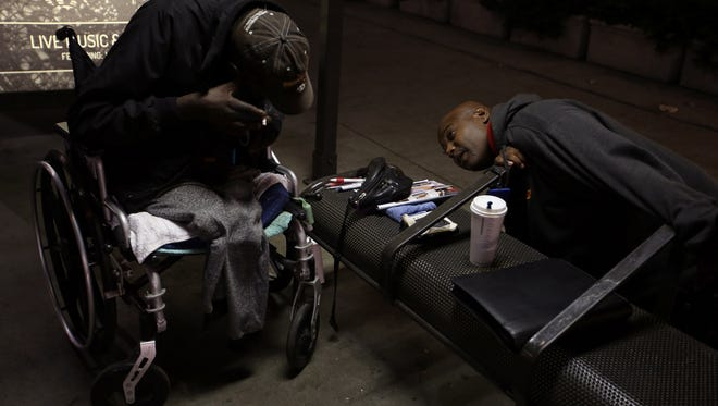 "At 4:30 a.m., Ruffin finds Eddie ""Snake"" Carter in pain, sheltering under a bus stop. He convinces the wheelchair-bound double amputee to go to a hospital. (Francine Orr/Los Angeles Times/TNS)"
