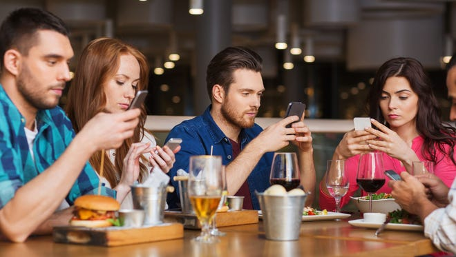 Friends with smartphones dining at restaurant.