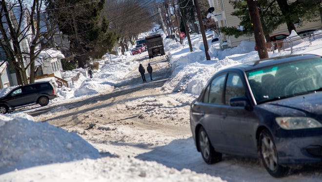 Cars and pedestrians navigate a snowy Oak Street in Binghamton on Thursday afternoon as winter storm cleanup continued throughout the day.