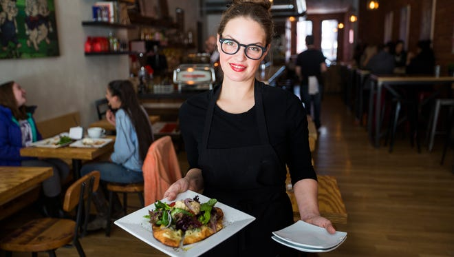 Eugenie Zynda holds a hummus and roasted vegetable flat bread pizzetta with heritage greens salad inside The Shop in downtown Binghamton on Thursday, March 16, 2017.