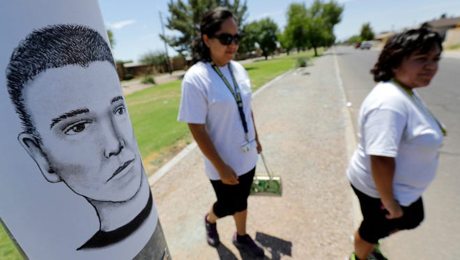 In this July 27, 2016, file photo, Phoenix neighborhood patrol officers Maribel Diaz Lopez, left, and Mario Ocampo walk a Maryvale neighborhood street in Phoenix, Ariz., to hand out an artist rendering of a suspected serial killer, as shown on the light pole, and block watch flyers. Authorities who have spent the last year investigating a serial killer stalking two predominantly Hispanic neighborhoods in Phoenix are experiencing a dry spell in the number of tips they received from the public. Friday, March 17, 2017 marks the one-year anniversary of the first attack carried out by the suspect believed responsible for killing seven people and wounding two others.