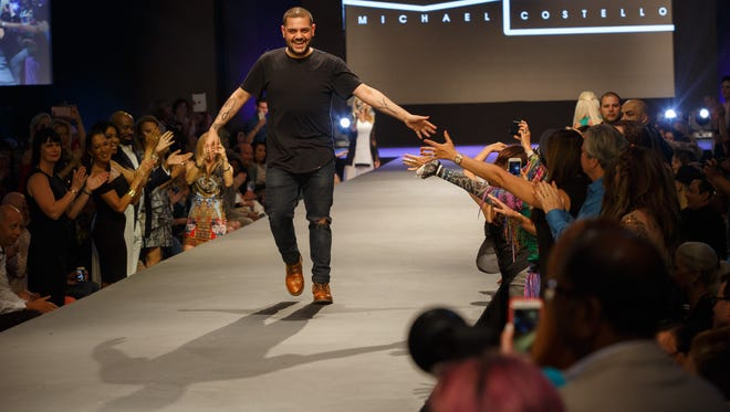 Michael Costello receives high fives on the runway after his show at Fashion Week El Paseo, Tuesday, March 21, 2017.