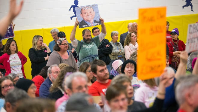 People hold signs during a town hall meeting held by Congressman Tom Reed at Broadway Academy in Elmira on Saturday, April 1, 2017.