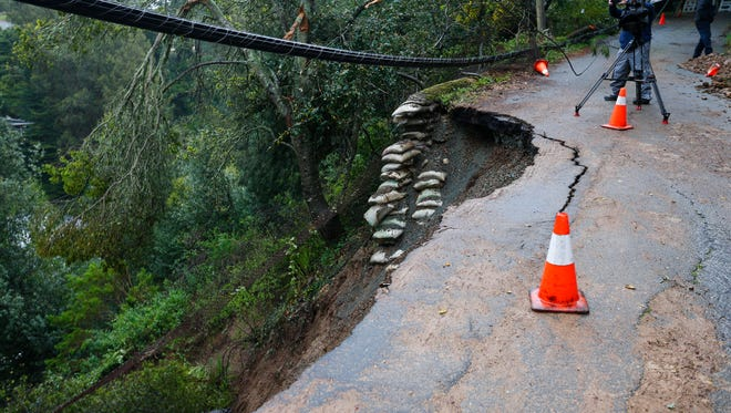 A landslide on Aitken Avenue after an overnight storm threatens homes Friday in Oakland.