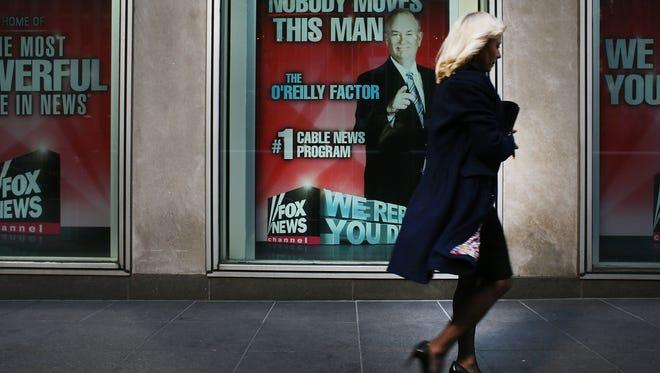 """An advertisement for Bill O'Reilly's top-rated Fox News show is displayed in the window of the News Corp. headquarters on April 5, 2017 in New York City.  Following allegations that he sexually harassed several women, over a dozen major advertisers, have pulled their ads from """"The O'Reilly Factor."""""""