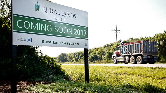 A truck passes by a sign for a proposed housing development to be called Rural Lands West in rural Collier County on Thursday, July 9, 2015.