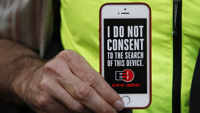 A man holds up his iPhone during a recent rally in support of data privacy outside the Apple Store in San Francisco. Watchdog groups are concerned that U.S. Customs and Border Protection agents are searching the phones and other devices of international travelers at borders and airports.