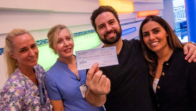 Eric Gaffoglio, center right, and his wife Maryam Pakdelan-Gaffogio, right, donate a check for $10,000 to CHOC on April 12, 2017 in Orange, Calif. Neonatal ICU nurses Debbie Vandevelde, left, and Cindy Salido were on hand to receive the check.