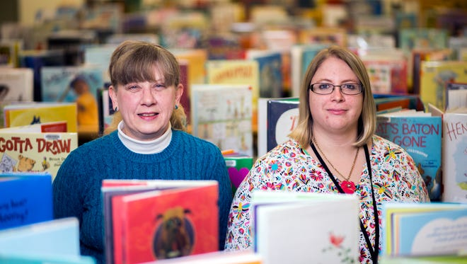 Debbie Catron, president of the Friends of the Broome County Public Library, left, and Broome County Library youth services librarian Kelsey Matoushek among the stacks inside the library's children's area.