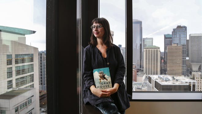 "Gabriella Page-Fort, the editorial director for AmazonCrossing, poses for a portrait on Wednesday, March 8, 2017, in Seattle, while holding a copy of the book ""The Gray House"" by Mariam Petrosyan."