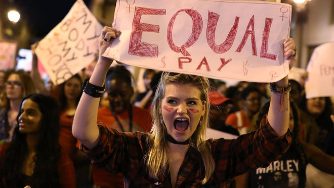 Clarissa Horsfall holds a sign reading, 'Equal Pay,' as she joins with others during 'A Day Without A Woman' demonstration on March 8, 2017 in Miami. Some states and cities are barring employers from asking job candidates their prior salaries to promote pay equity between men and women.