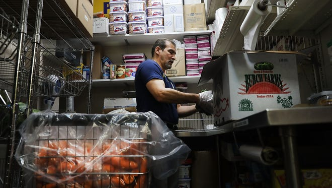 An employee sorts food at the Reaching Out Community Services food pantry in Brooklyn on May 15, 2017 in New York City. The popular Brooklyn food pantry feeds over 4,000 New Yorkers per month while offering a host of other services for those in need. Agencies throughout the nation that feed, shelter and care for the needy are increasingly nervous about proposed cuts to their programs if President Donald Trump's budget passes.