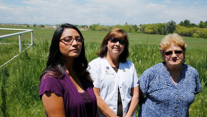 FILE - In this Tuesday, May 31, 2016 file photograph, Nelly Morales, from left, Michelle Young and Dawn Stein are photographed on Stein's property next to an oil well complex in Greeley, Colo. Residents of the neighborhood sued the state of Colorado on Friday, May 19, 2017, saying oil and gas regulators have not done enough to protect them from the disruption and danger of the big energy facility being constructed in a pasture surrounded by homes west of Greeley. (AP Photo/Brennan Linsley, File)