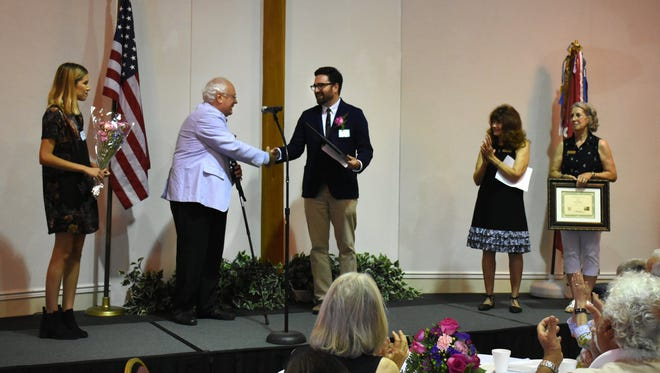 Artist of the Year honoree Austin Bell, center, receives congratulations from MIFA president Clark Lindberg. MIFA awarded its Artist of the Year award at a luncheon Saturday at the Wesley United Methodist Church.