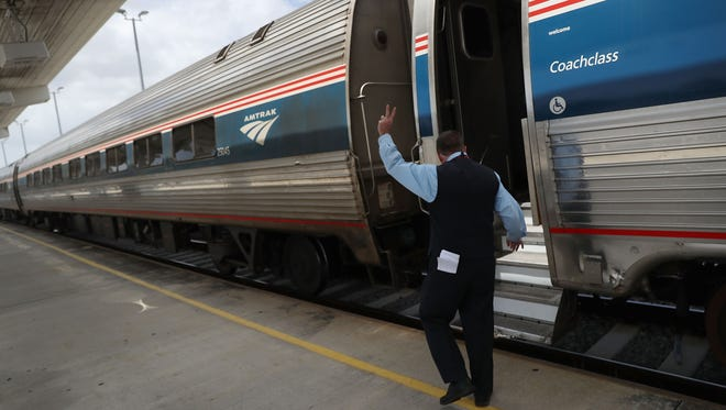 An Amtrak employee prepares to board the train as it pulls out of the Miami station on May 24, 2017 in Miami, Florida.