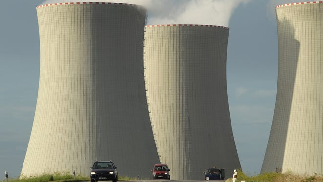 Cars drive by the four cooling towers of the Temelin nuclear power plant on August 11, 2011 near Temelin, Czech Republic.