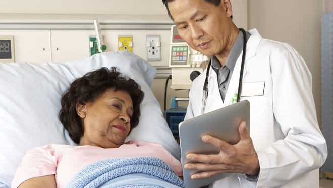 Photo illustration shows a doctor using a digital tablet computer with a patient