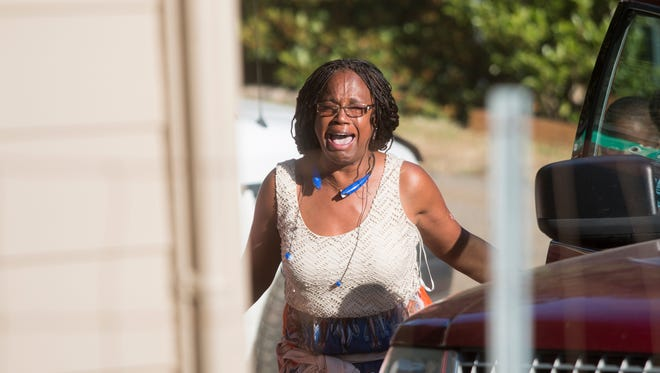 Mamie Randle screams shouts of joy as she walks up to her newly restored house.