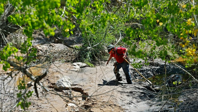 Mella Smith of the Tonto Rim Search and Rescue walks through thick mud as she scours the area near the Water Wheel campground in the Tonto National Forest Monday, July 17, 2017 in Payson. A flash flood at a popular swimming hole north of Payson killed nine people.