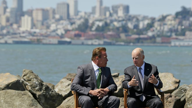 California Gov. Jerry Brown, right, and former Gov. Arnold Schwarzenegger, left, talk before a climate bill signing on Treasure Island on Tuesday in San Francisco.