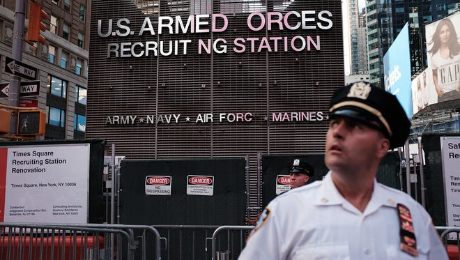"""A police officer stands guard as dozens of protesters gather in Times Square near a military recruitment center to show their anger at President Donald Trump's decision to reinstate a ban on transgender individuals from serving in the military on July 26, 2017 in New York City. Trump citied the """"tremendous medical costs and disruption"""" for his decision."""