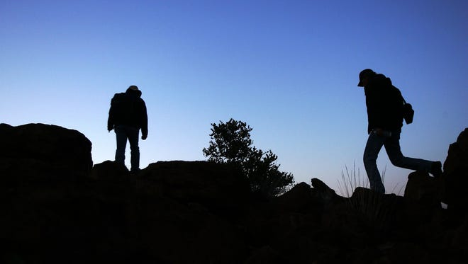 FILE - Hikers are seen hiking on a trail.