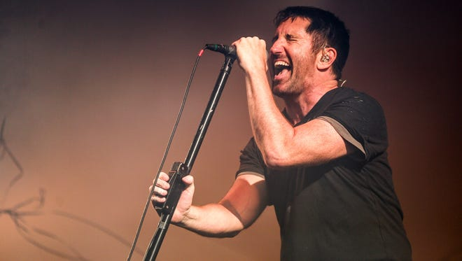 Trent Reznor, seen here performing in Los Angeles on July 23, still has the same body language on stage he did back in the 1990s. The biggest change from Nine Inch Nails' early days? You can actually see his face, courtesy of a haircut several years back.
