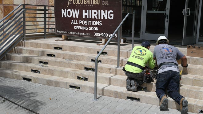 A now-hiring sign is posted on the steps of a business as workers prepare the building for a new restaurant  July 7 in Miami.