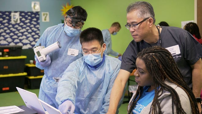Dr. Peter Young, an oral surgeon, leads a team looking at a patient's X-rays to see what procedure is needed March 24 in Riverside, Calif., as part of a clinic organized by California-based Adventist Medical Evangelism Network (AMEN).