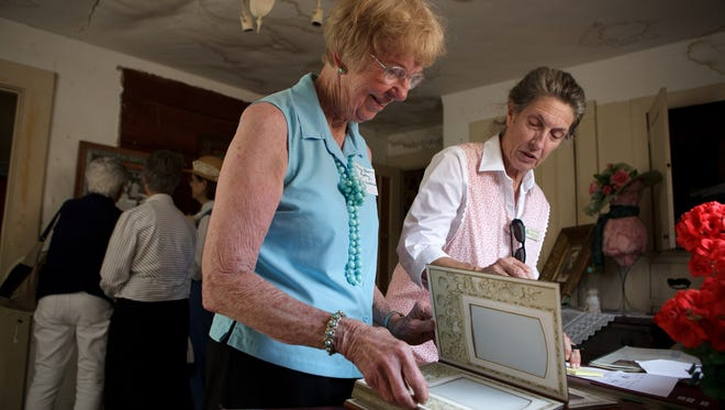 Mary Olsen-Rydberg, from left, helps Patricia Conklin identify family members in an old photo book from the Stagecoach Inn Museum's archive during the Borchard family reunion at the Oxnard Historic Farm Park on Saturday.