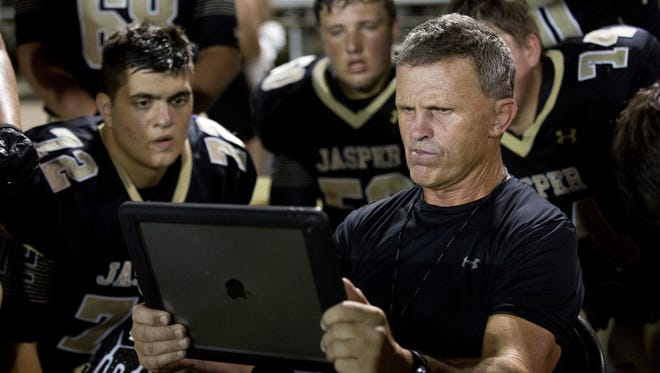 Jasper coach Tony Ahrens reviews a play on a tablet screen in 2016.