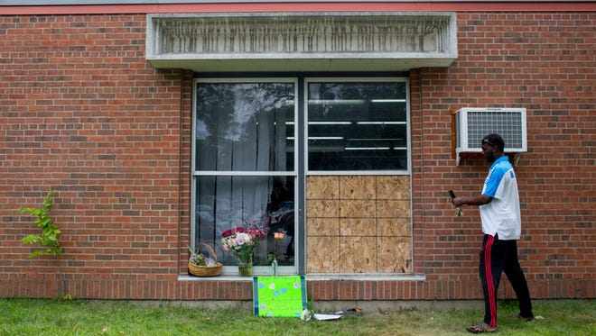 Abdul Mohamed photographs the damage outside of the Dar Al Farooq Islamic Center in Bloomington, Minn., on Sunday, Aug. 6, 2017.  An explosion damaged a room and shattered windows as worshippers prepared for morning prayers early Saturday.