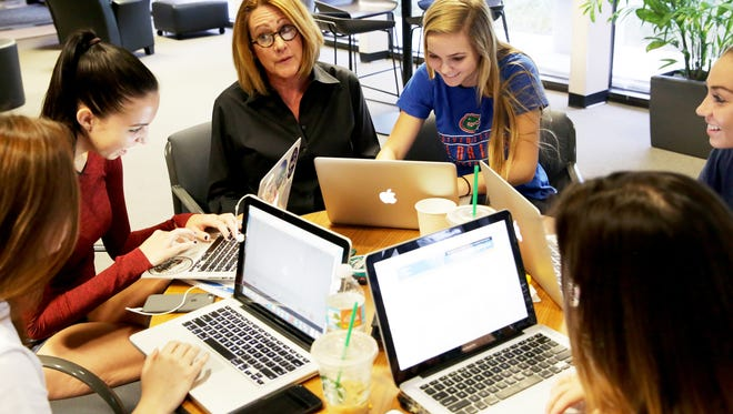 Executive Director Susan Zumstein, center, works with students at the Quest College Success offices in Naples on Wednesday, Oct. 12, 2016. Quest is designed to help high school students prepare for college.